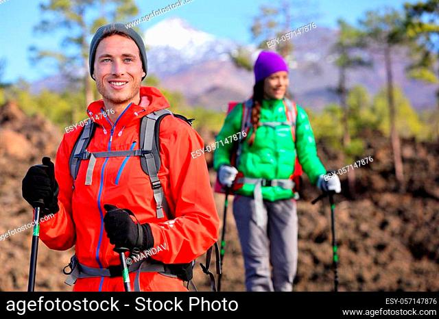 Hiking hikers couple - healthy active lifestyle. Hiker couple hiking in beautiful mountain nature landscape. Woman and man hikers walking during hike on volcano...