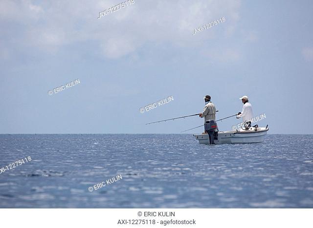Fishermen standing in a boat fishing; Tahiti