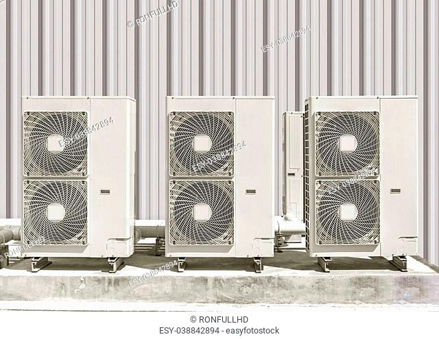 Air compressor on concrete pedestal with siding wall background