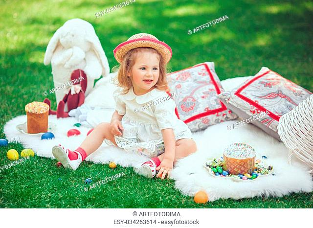 Cute little smiling baby girl in park on green grass. Poster for Easter holiday. Selective focus on child