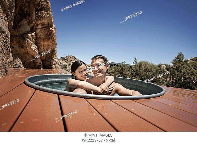 A man and woman on the terrace of an eco home, a low impact house in the desert landscape, in a sunken hot tub