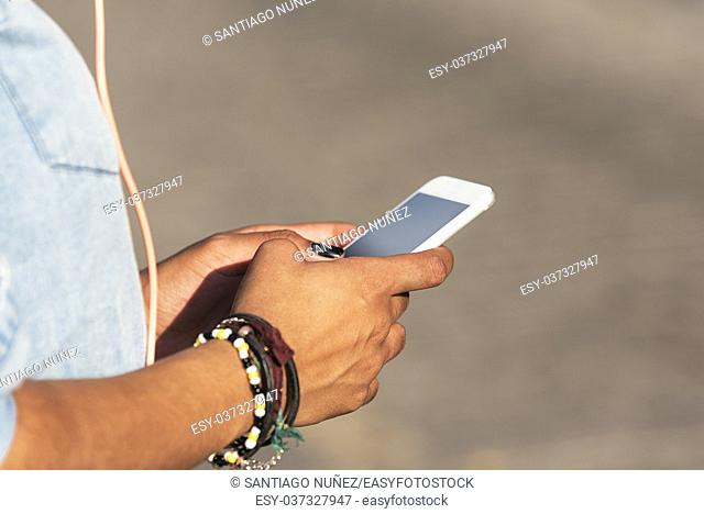 Close up of woman using mobile in the street. Communication concept