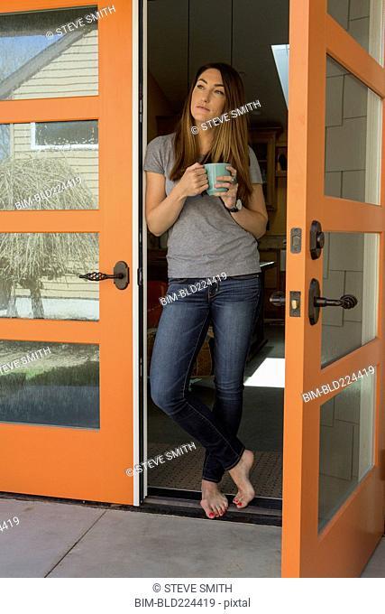 Woman standing barefoot in doorway drinking coffee
