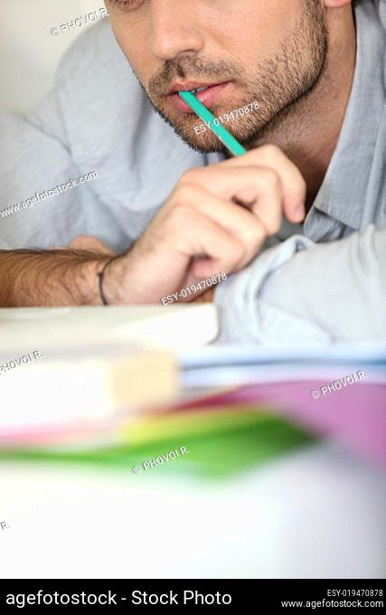 Closeup of a man working with a pen in his mouth