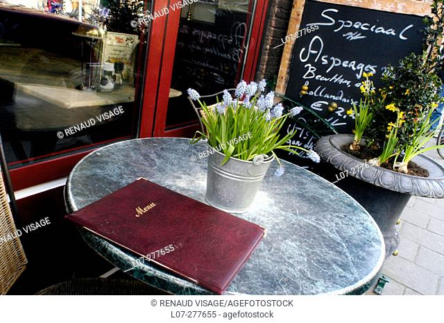 Restaurant table with menu and flower pot. Amsterdam. Holland