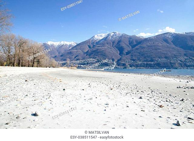 Beach with white sand an alpine lake with snow-capped mountains in ascona