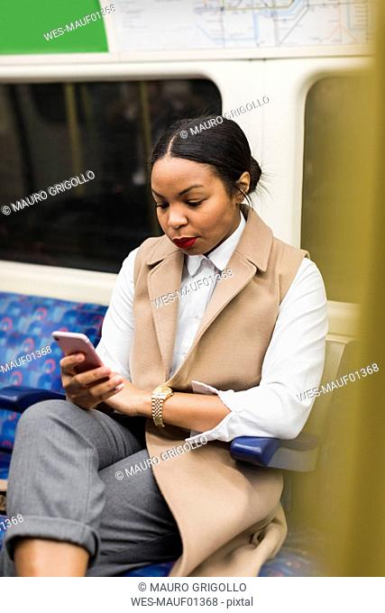UK, London, portrait of businesswoman in underground train looking at cell phone