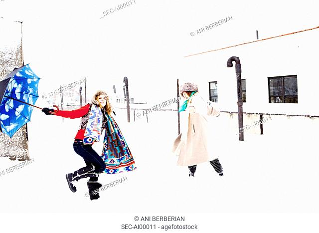 Women with sky patterned umbrella dancing on snow covered rooftop