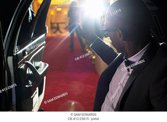 Celebrity in limousine arriving at red carpet event and waving to photographing paparazzi