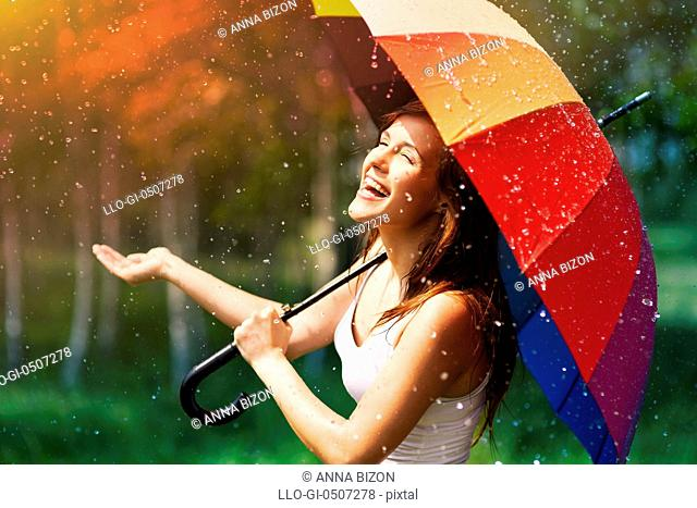 Laughing woman with umbrella checking for rain, Debica, Poland
