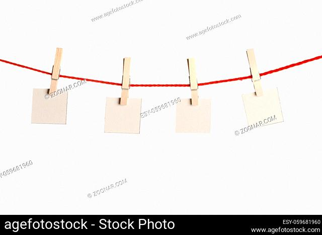 Set of four red blank paper notes held on a string with clothespins isolated on white background