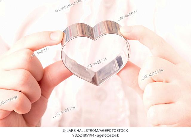 Little girl holding heart shaped cookie cutter in her hands. Conceptual image of childhood, love and affection