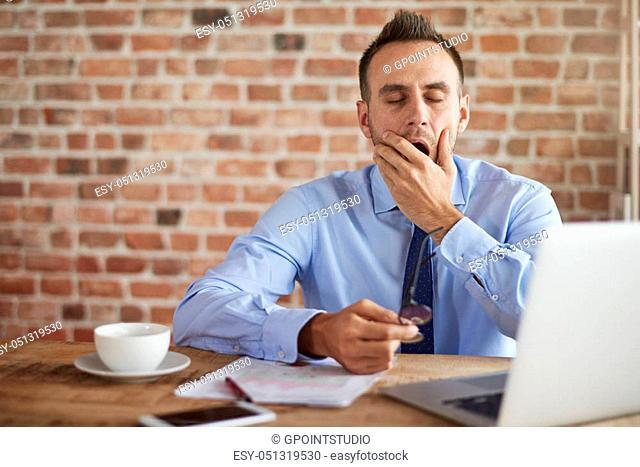 Yawing man behind the desk