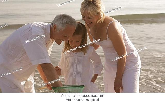 grandparents and granddaughter on beach with fishing net