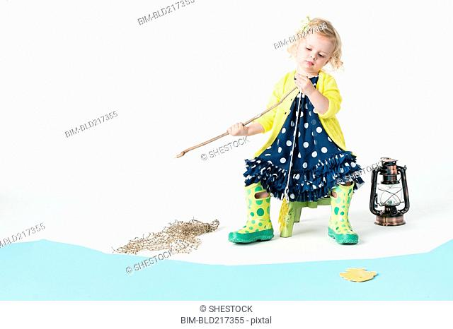 Girl playing fishing with toy fish