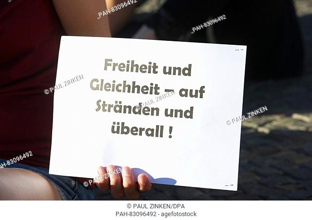 A participant holds up a sign written with 'Freedom and equality - on beaches and everywhere' during a Beach Party announced on Facebook at Pariser Platz in...