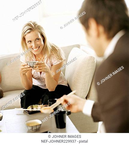 A man and a woman eating sushi