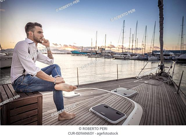 Young man using smartphone on yacht, Cagliari, Sardinia, Italy