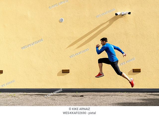 Sportive man exercising at yellow wall with CCTV camera