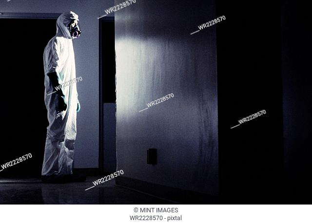 Man wearing a hazardous material protective clean suit, facing bright light in hallway