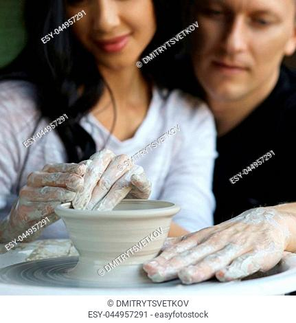 Romatic couple working on potter wheel and making or sculpting clay pot. Focus on hands