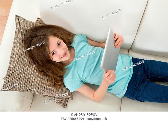 High Angle View Of Girl Lying On Sofa Using Digital Tablet In Living Room