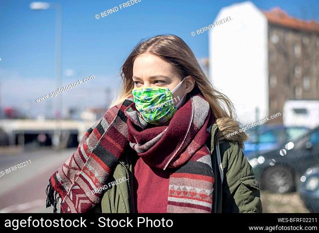 Portrait of young woman wearing mask in the city