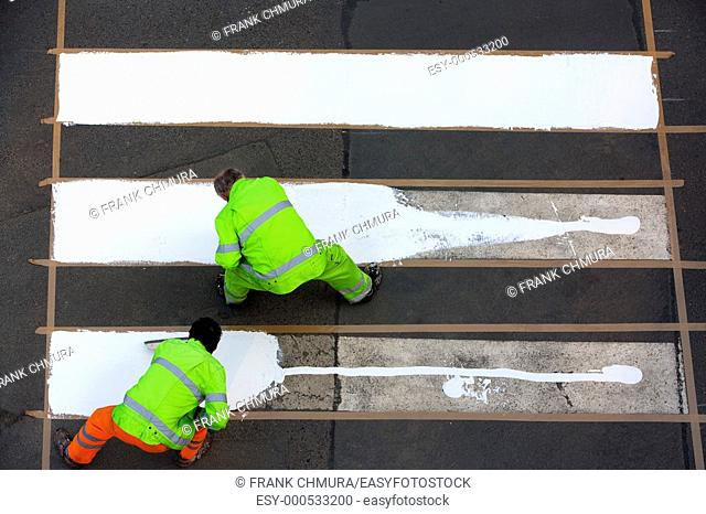workers painting crosswalk with white colour - view from above