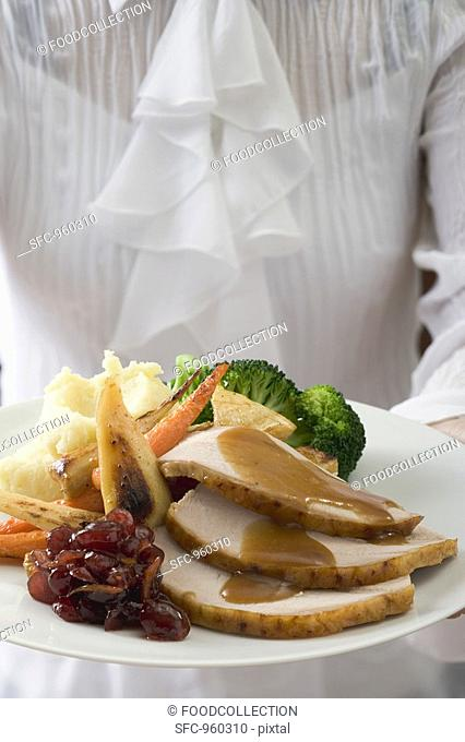 Woman serving turkey breast & accompaniments, Thanksgiving USA