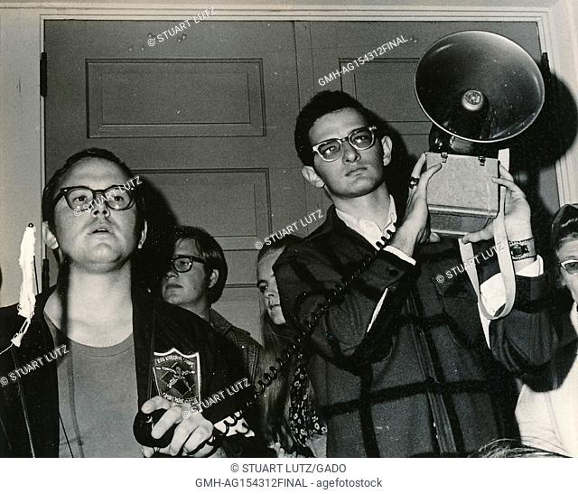 Student wearing hippie attire, including a disheveled military jacket, speaking into the microphone of a bullhorn loudspeaker during an anti Vietnam War student...