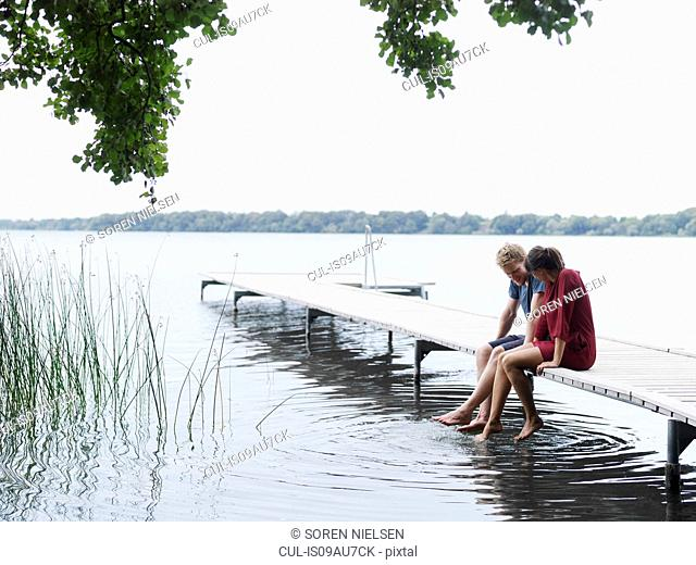 Couple sitting on pier side by side dipping toes in water, Copenhagen, Denmark