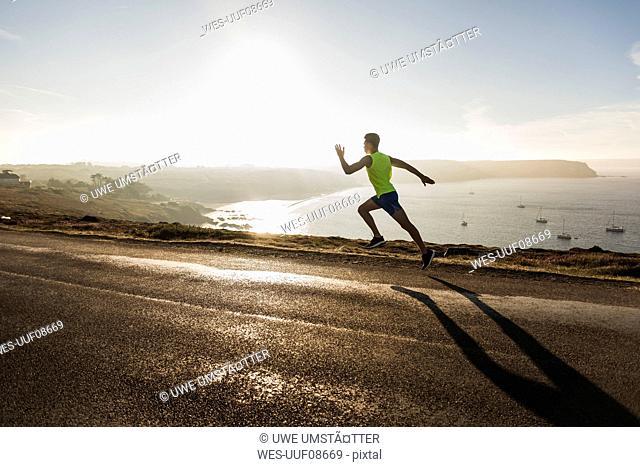 France, Crozon peninsula, young man running on coastal road