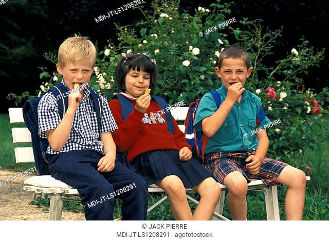 Children on a bench and eating a biscuit