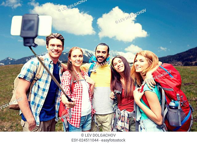technology, travel, tourism, hike and people concept - group of smiling friends walking with backpacks taking picture by smartphone on selfie stick over natural...