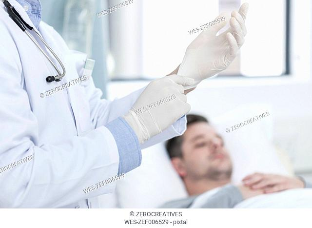 Doctor putting on gloves, patient in background