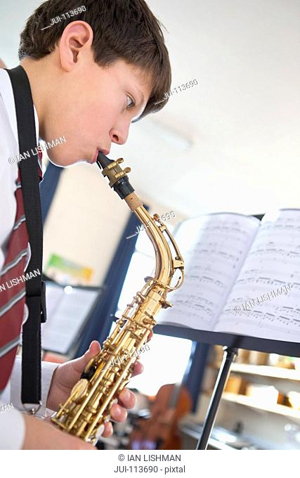 High school student playing saxophone at music stand in music class