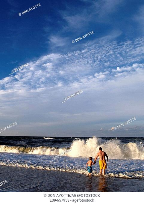 Father & Son playing in the waves in , NC, USA