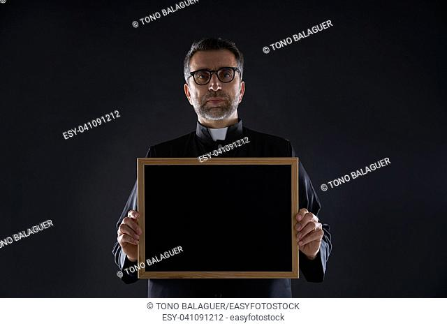 Priest holding empty blackboard copy space isolated on black