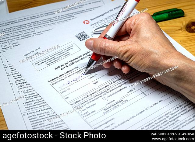 30 March 2020, Mecklenburg-Western Pomerania, Schwerin: ILLUSTRATION - A woman fills out an application form for short-time work allowance. On 31.03