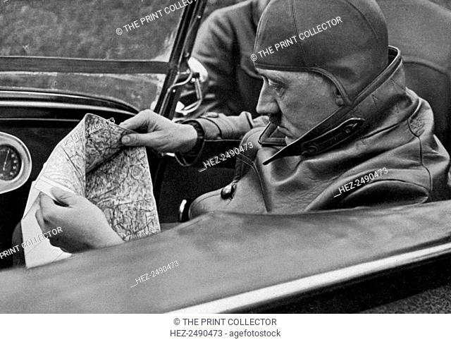 Adolf Hitler specifies the travel route, Germany, 1936. Hitler (1889-1945) consulting a road map during a car journey. A print from Adolf Hitler