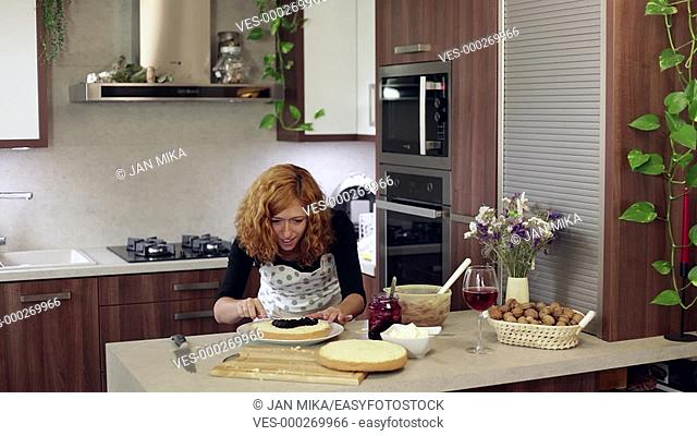 Young happy woman putting a jam on homemade cake in the kitchen at home