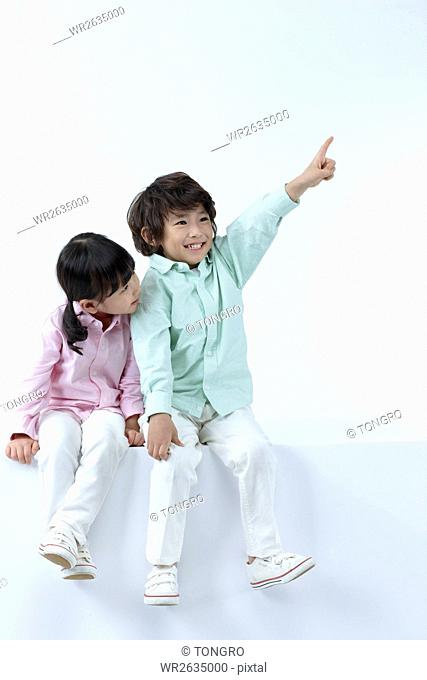 Smiling boy and girl sitting side by side looking up