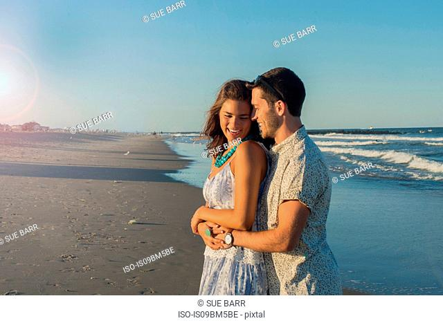 Romantic young couple hugging on beach, Spring Lake, New Jersey, USA