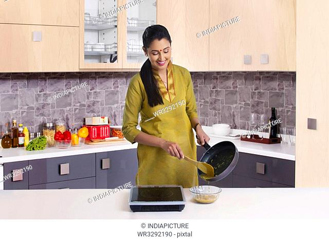 Portrait of woman cooking in kitchen