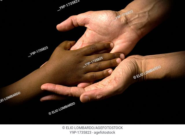 White woman's hands receive the black child's hand