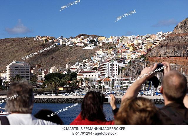 Tourists on a ferry taking pictures of San Sebastian de La Gomera, La Gomera Island, Canary Islands, Spain, Europe