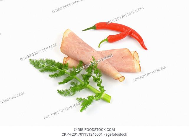 slices of ham and red chili peppers on white background