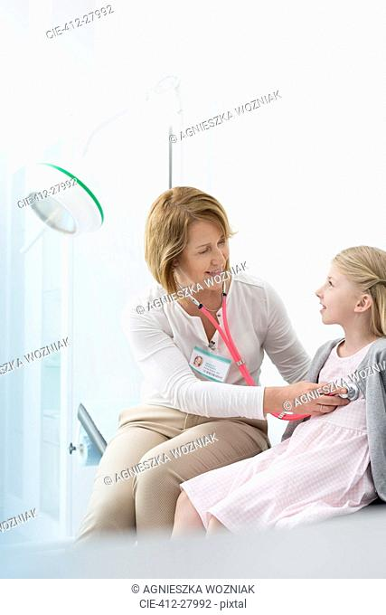 Pediatrician using stethoscope on girl patient in examination room