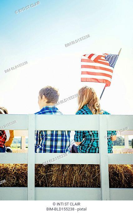 Caucasian children waving American flag on hay ride