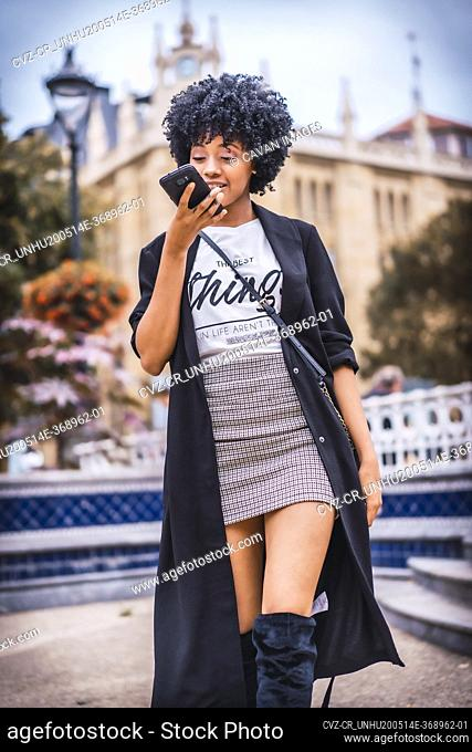 Street style, girl with afro red hair talking on the phone in the city